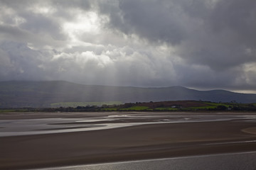 View of sun shining over estuary in North Wales