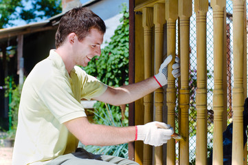 Young man painting wooden fence in the garden