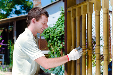 Young man painting wooden fence in the garden sitting near it