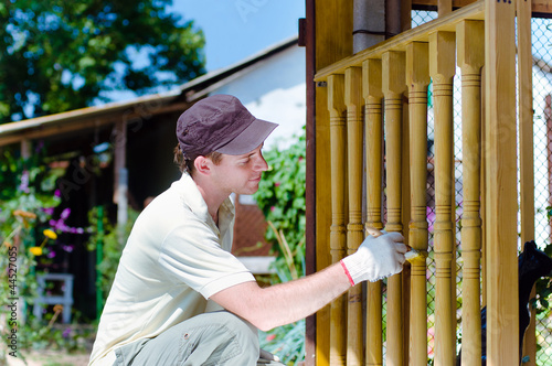 Young man painting wooden fence in the garden smiling