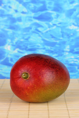 Ripe appetizing mango on woven cloth on water background