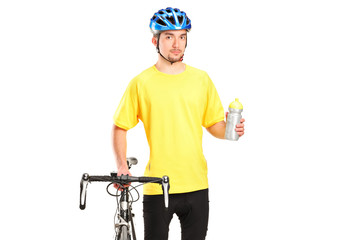 Bicyclist posing next to a bicycle and holding a bottle