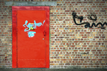 Red flashy metallic door on brick wall