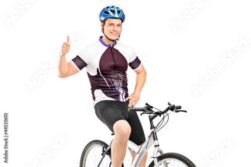 A smiling bicyclist posing on a bicycle and giving a thumb up