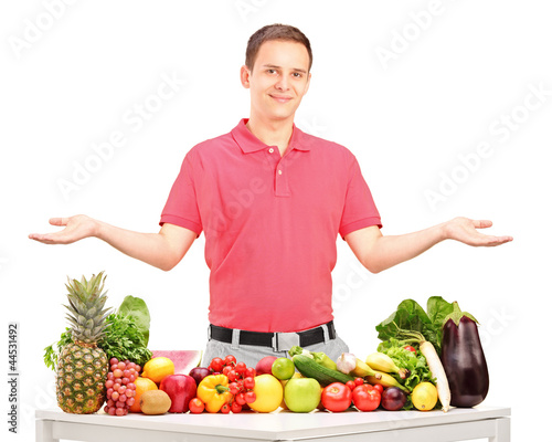 Handsome guy gesturing with his arms behind a table with fruits