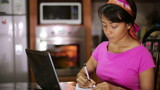 woman with laptop writing recipe from internet in kitchen