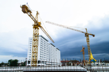 Construction site with crane near building on Cloudy storm backg