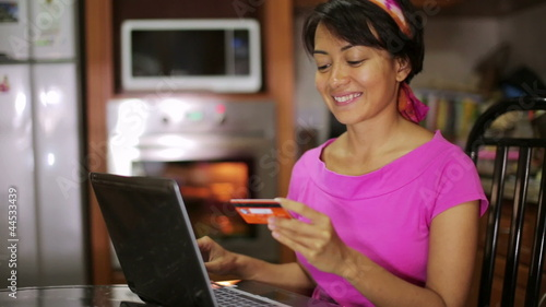 woman buying with credit card, online shopping in kitchen