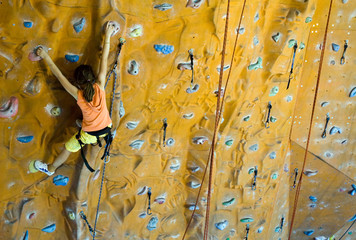 Climbing teenager girl to the top of wall