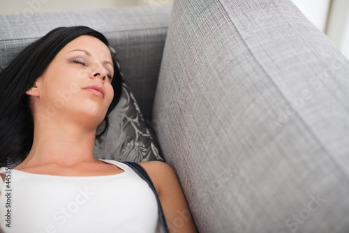 Young woman sleeping on divan
