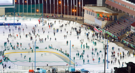 Ice skating rink whith motion blurred large group of skating peo