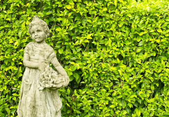 Small garden statue in a garden on a city front yard.
