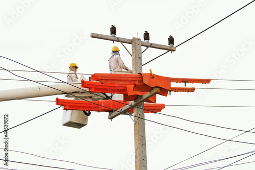 An electrical power utility worker in a bucket fixes the power l