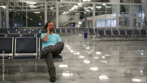 young man talking on phone at airport