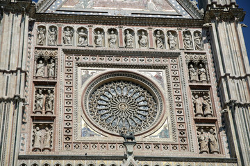 antique rose window of a church and the statues