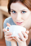 Blue-eyed woman with cup of tea has a rest at the restaurant