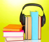 Headphones on books on green background