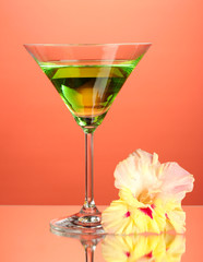 glass with cocktail and gladiolus bud on red background