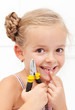 Little girl smiling holding her missing tooth with pliers