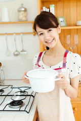 Beautiful young woman in the kitchen. Portrait of asian.