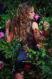 an attractive woman standing among the rose bushes