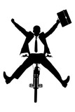A silhouette of a happy businessman on a bicycle