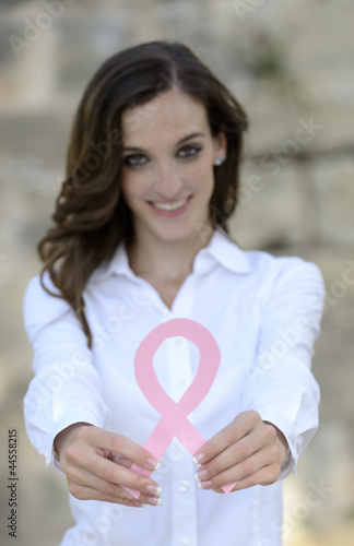 woman holding breast cancer support ribbon