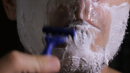 man shaves disposable razor close up