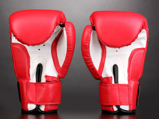 Red boxing gloves on grey background