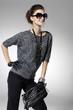 young fashion model in sunglass holding handbag