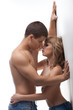 Strong man and sexy girl posing topless in jeans