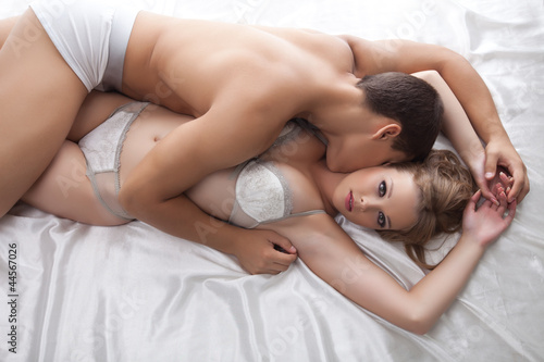 Young lovers lay in bed - only lingerie
