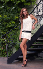 Beautiful woman in white dress standing near the metal stairs