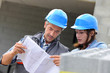 Closeup of engineers reading plan on building site