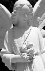 angel sculpture with chaplet and  posy of roses