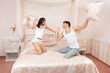 Young couple fighting pillows on bed