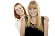 young beautiful red and blond haired girls hide behind back