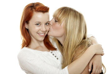 young beautiful red and blond haired girls kissing cheek