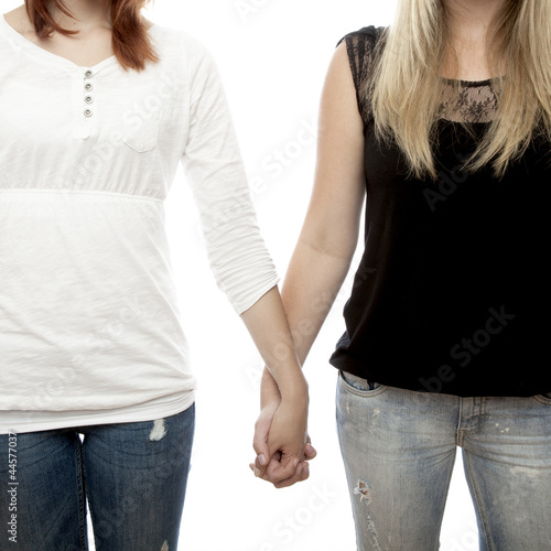beautiful red and blond haired girls holding hands close up