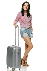 Full length of casual female standing with suitcase