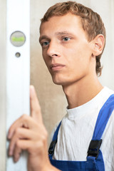 Young carpenter man worker with level
