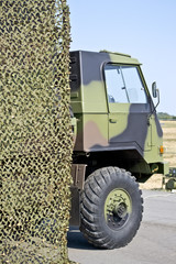 military vehicle hung with camouflage netting