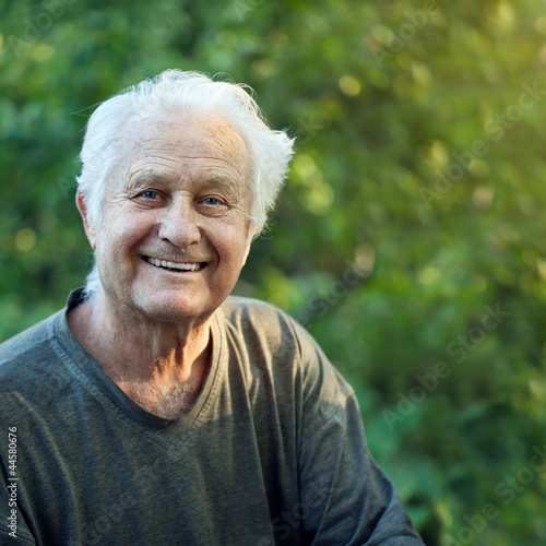 Portrait of a positive elderly man in a garden.