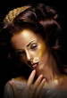 Paint. Fantasy. Glamor. Creative gold make-up, beauty woman face
