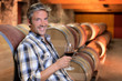 Smiling winemaker standing in wine cellar with glass