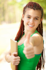 cheerful student girl with thumb up, outside
