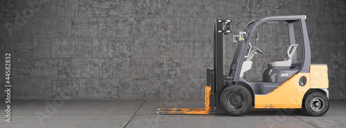 Leinwandbild Motiv Forklift standing on industrial dirty concrete wall background