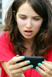 Girl in disbelief over mobile or cell phone text