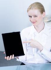 blonde frau zeigt auf ein touchbook