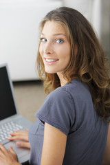 Sweet young lady on couch with laptop